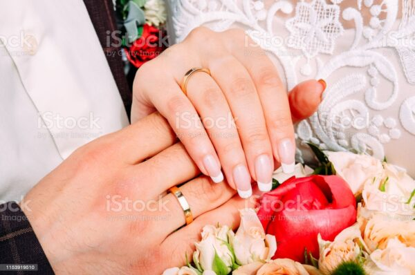 Newly married couple holding hands together wearing wedding rings with beautiful bridal manicure